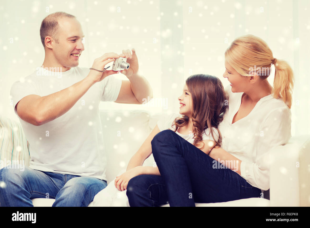 happy family with camera taking picture at home - Stock Image