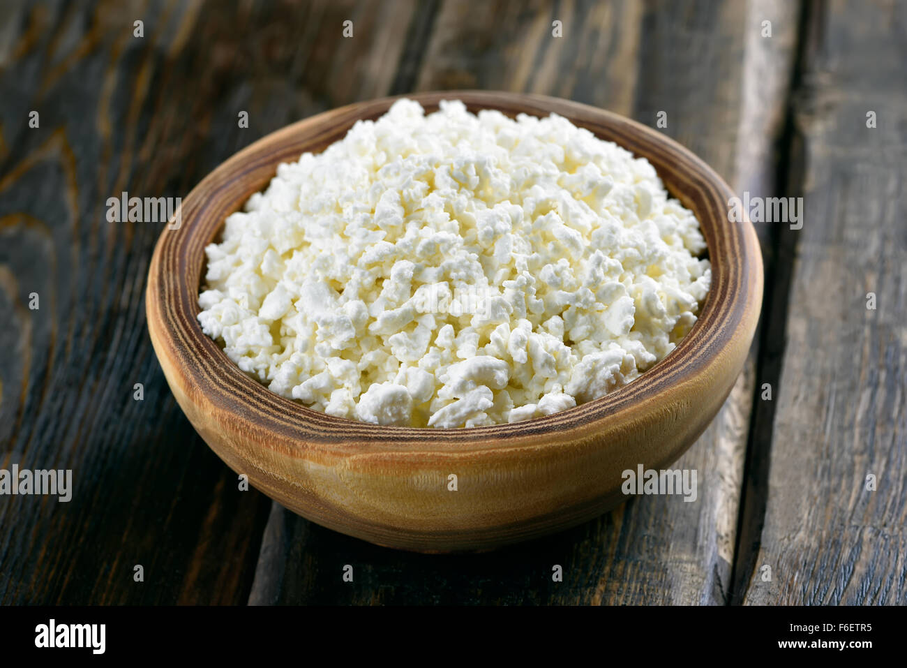 Curd in bowl on wooden table, close up view - Stock Image