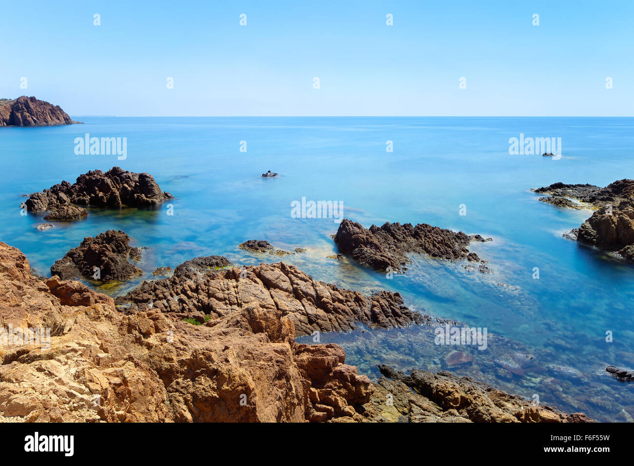 Esterel mediterranean red rocks coast and water sea in a long exposure seascape photography. Cote Azur near Cannes, - Stock Image