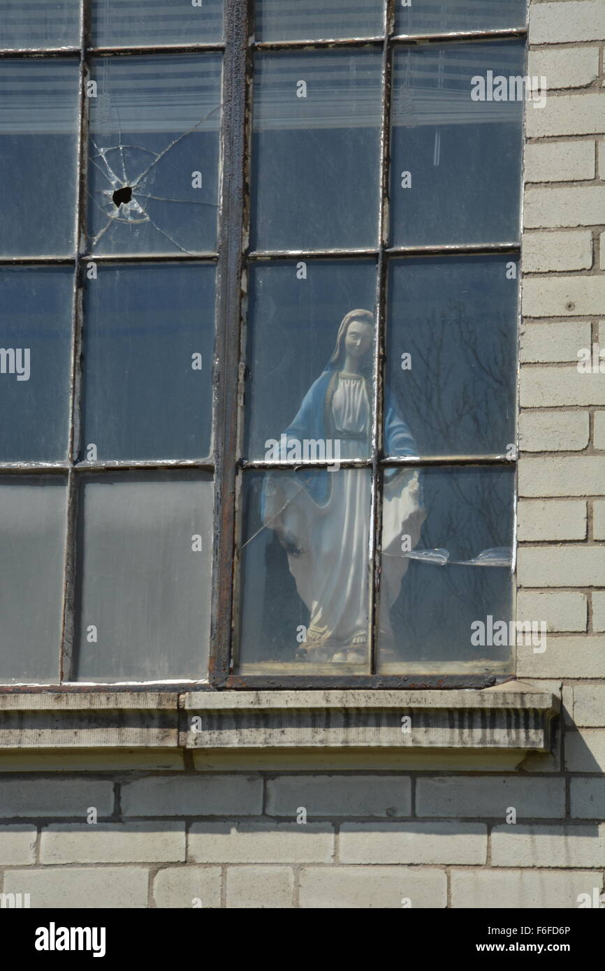 Bullet hole in St. Adalbert church window with a statue of Jesus in the south side neighborhood of Pilsen in Chicago. - Stock Image