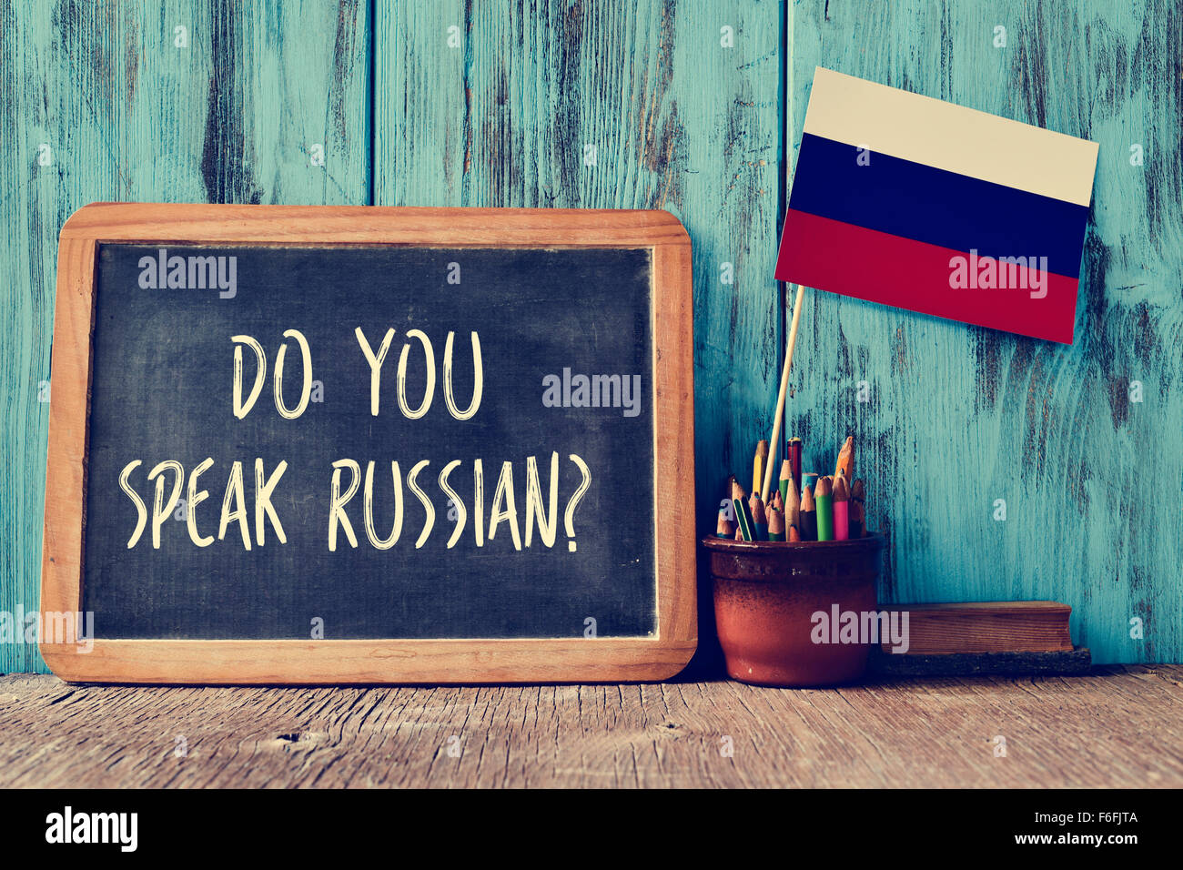 a chalkboard with the question do you speak russian? written in it, a pot with pencils, some books and the flag - Stock Image
