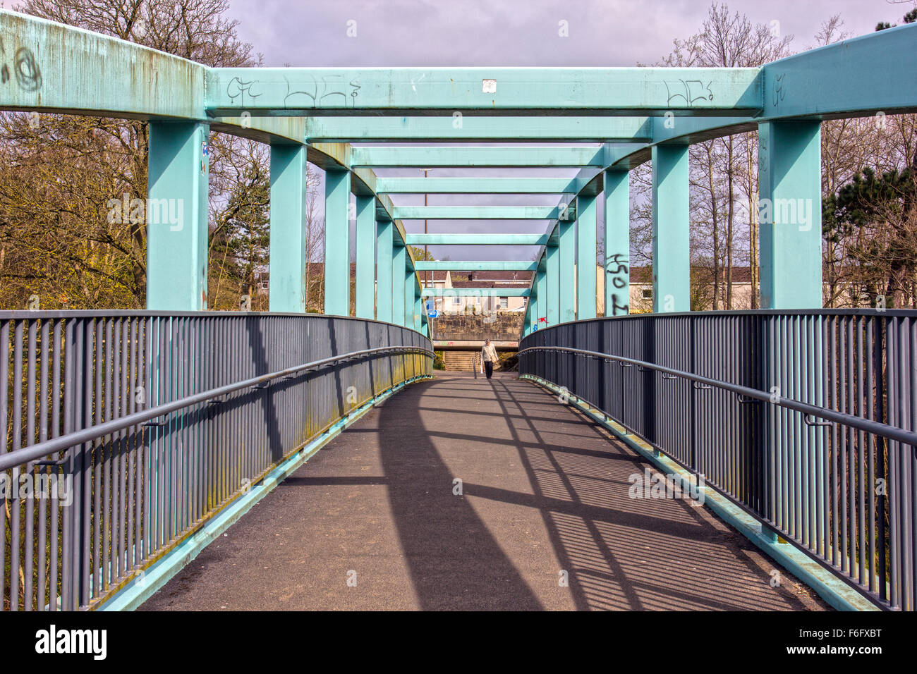 person crossing a steel bridge in Livingston West Lothian - Stock Image
