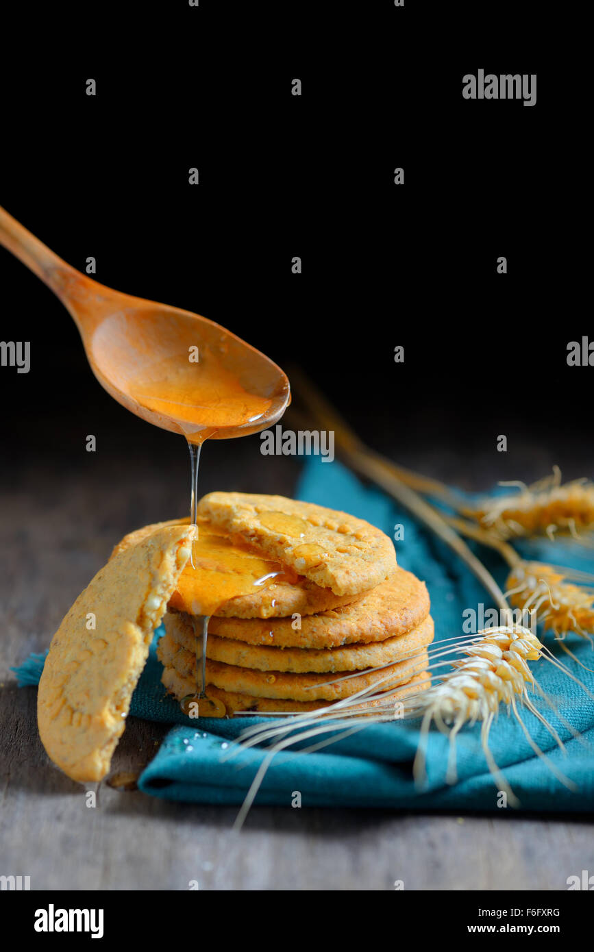 crispy cereal cookies and honey on rustic wooden table - Stock Image