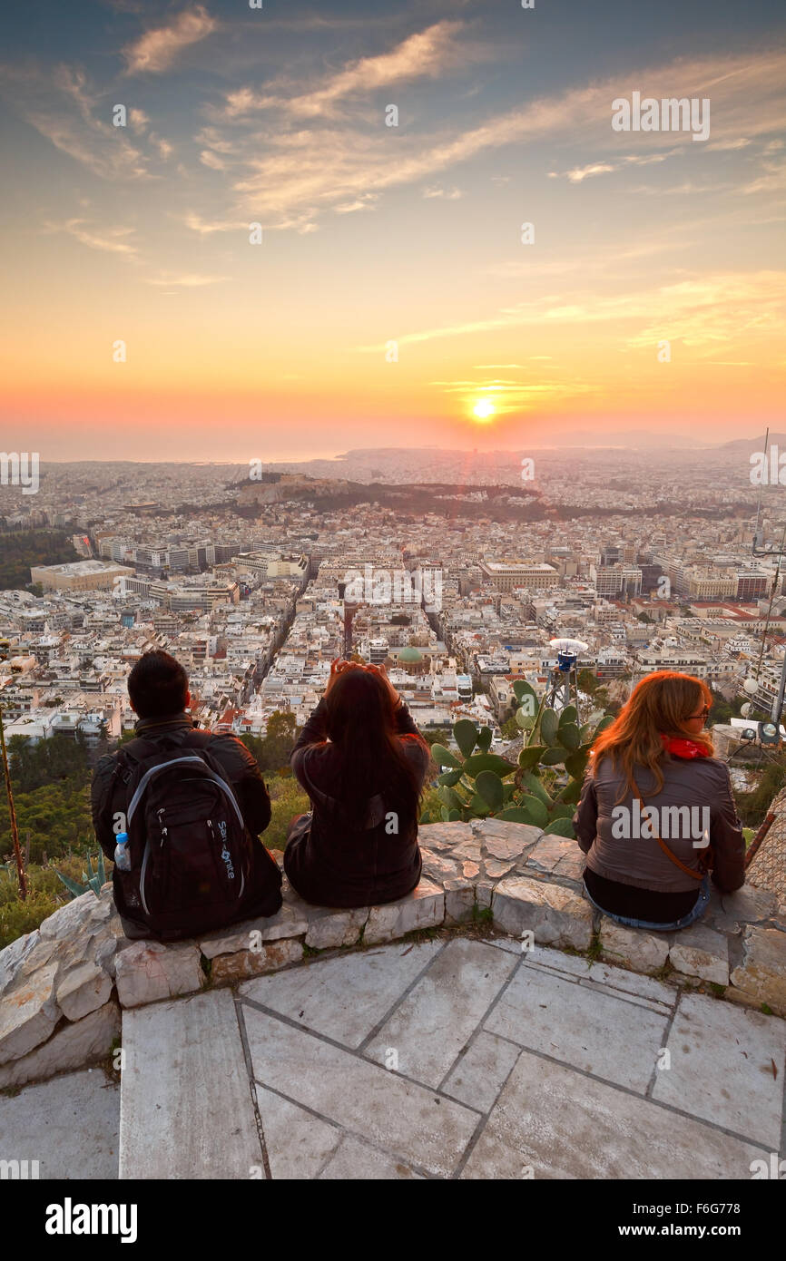 Tourists watching sunset over city of Athens and Acropolis from Lycabettus Hill - Stock Image