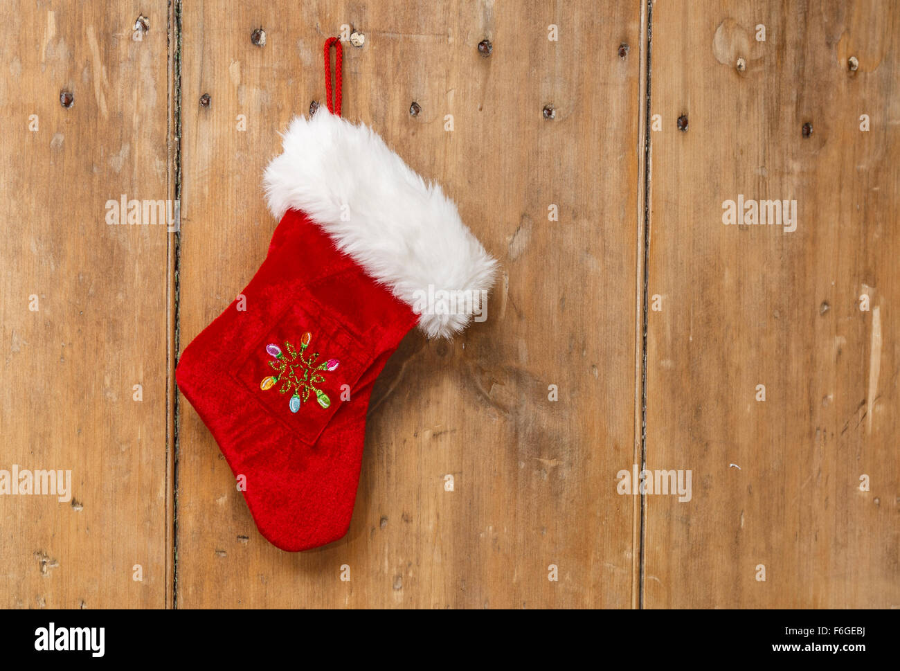 Christmas stocking hanging on an old pine wooden door - Stock Image