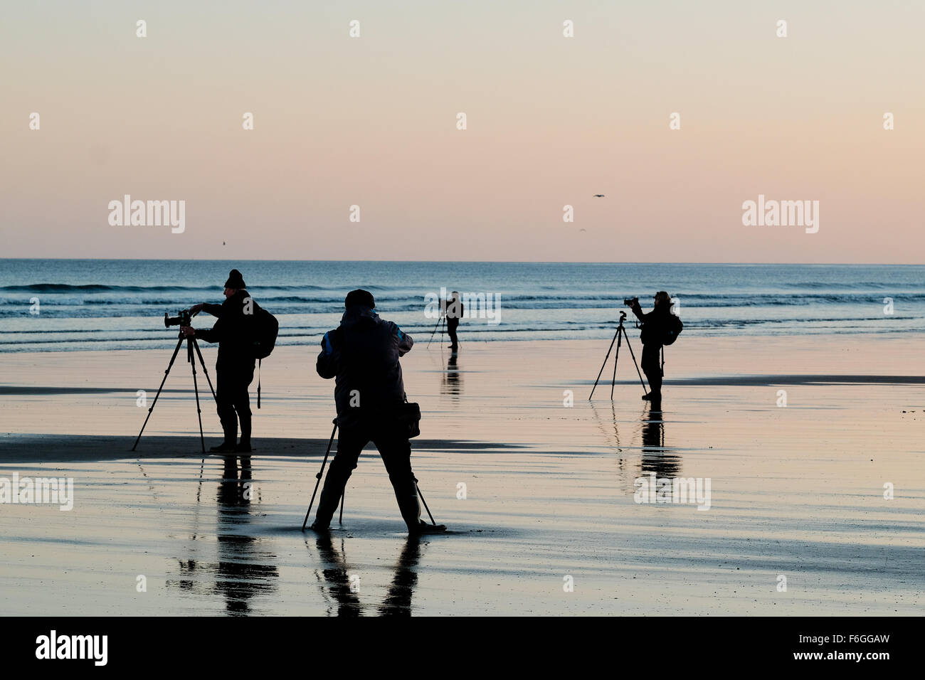 Four photographers are silhouetted as they line up their shots on the beach at Saltburn-by-the-Sea, UK. - Stock Image