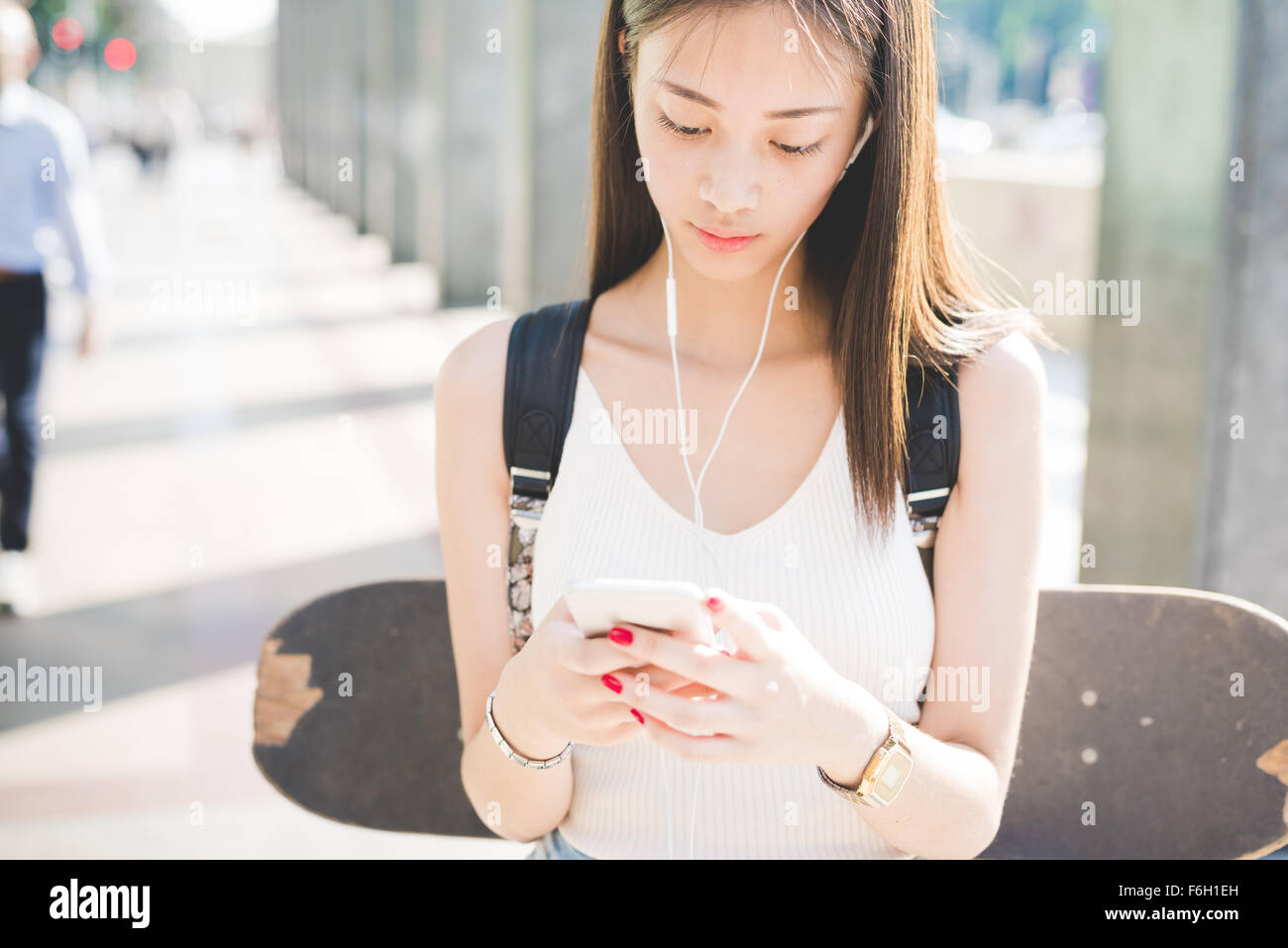 Half length of young handsome asiatic long hair woman skater walking in the city, listening music with earphones, Stock Photo