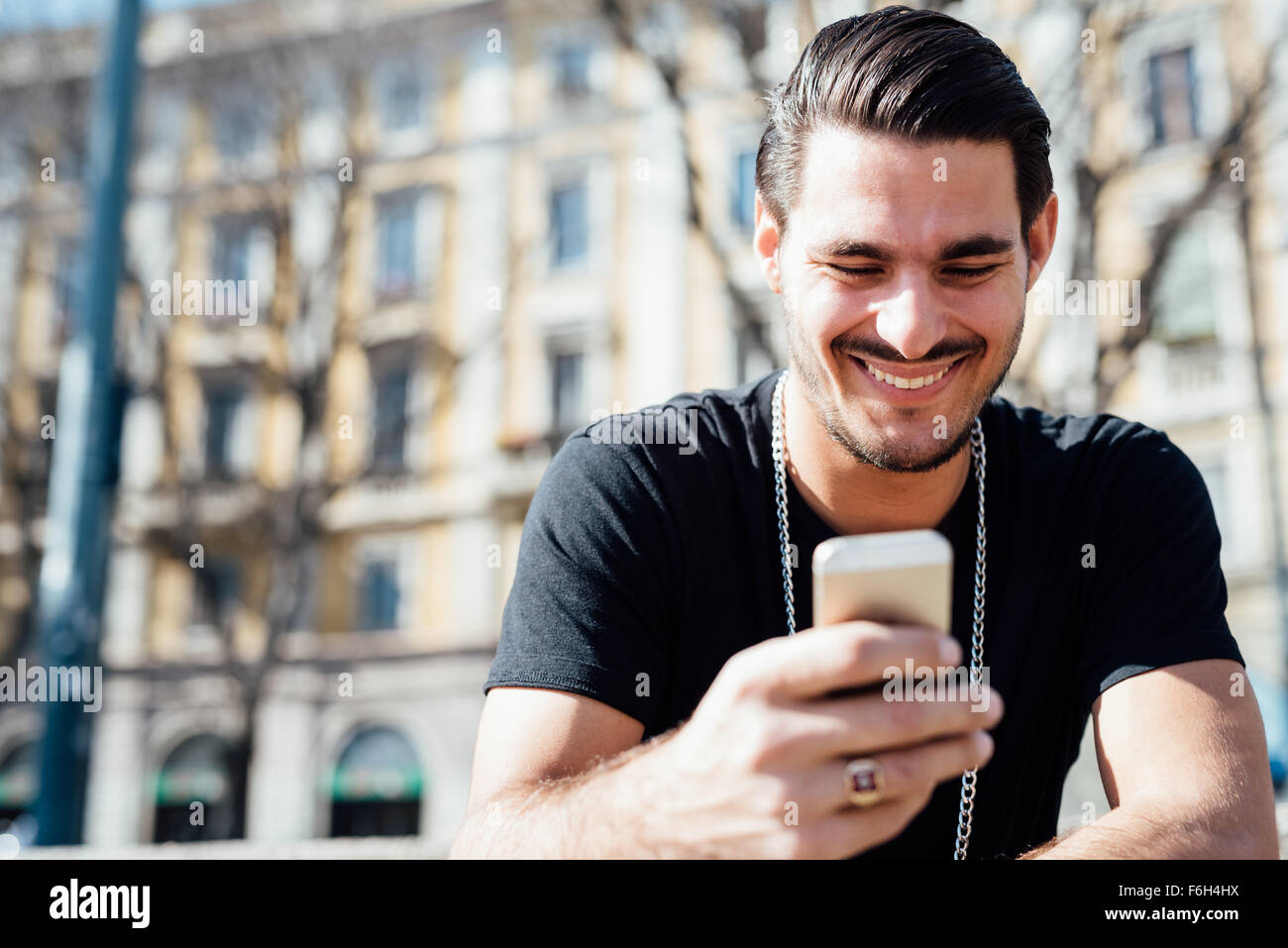 Portrait of a young handsome italian boy using a smartphone connected online, looking downward the screen, smiling - Stock Image