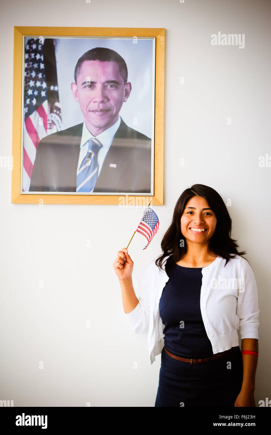 Patriotic Latina Woman's Naturalization, becoming a US Citizen next to a picture of Barrack Obama - Stock Image