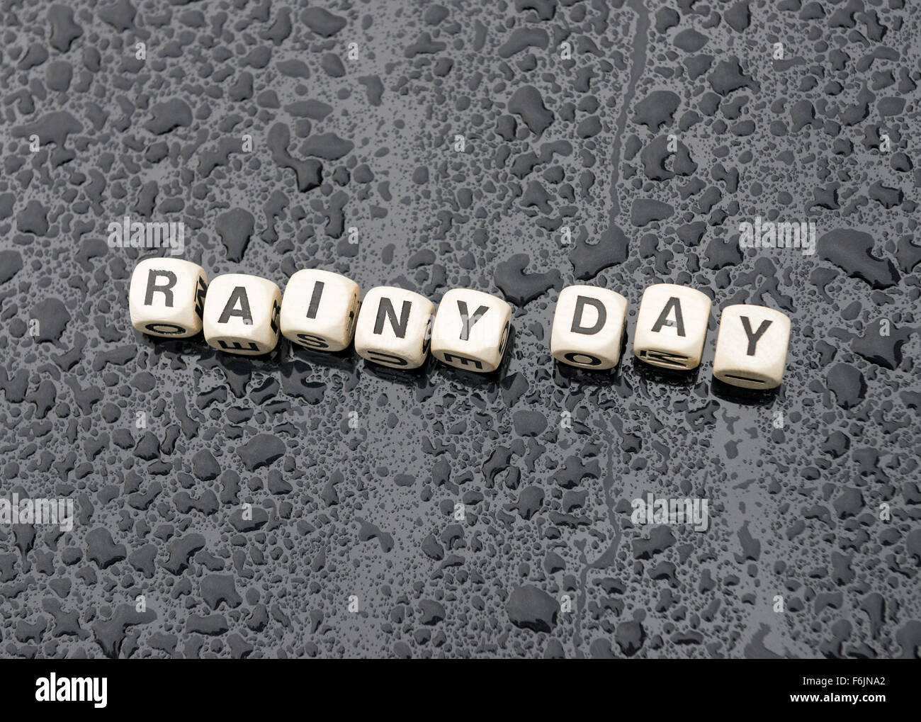 'Rainy Day' spelt out on a rain soaked car bonnet. - Stock Image