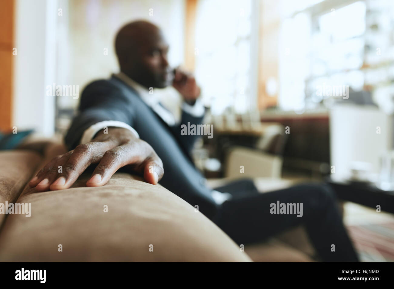 African businessman sitting in lounge area at hotel reception talking on mobile phone, focus on hand. - Stock Image