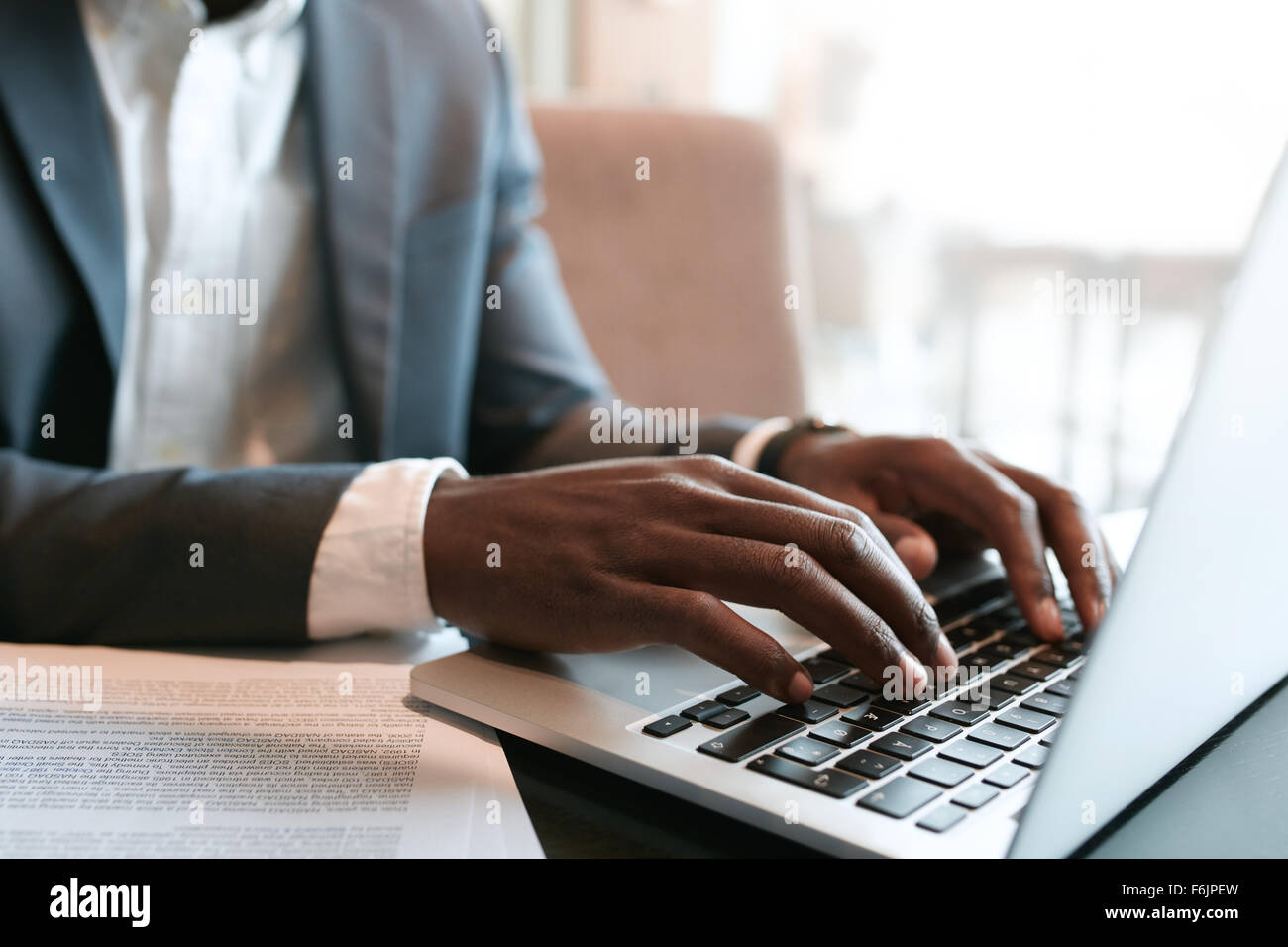 Businessman working on laptop with some documents on table. Close up on male hands typing on laptop keyboard. - Stock Image