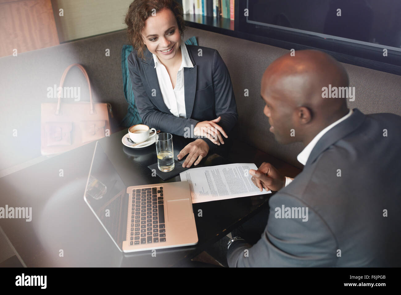 Shot of two young business colleagues working together at coffee shop. Business partners meeting at a cafe. - Stock Image