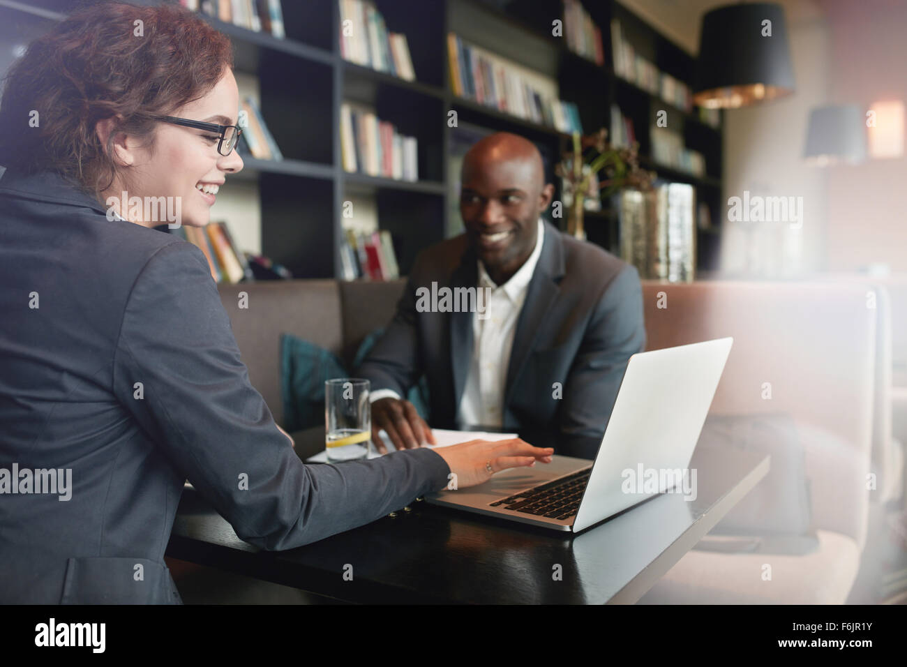 Young businesswoman showing presentation on laptop to her business partner. Happy executives in a meeting at restaurant - Stock Image