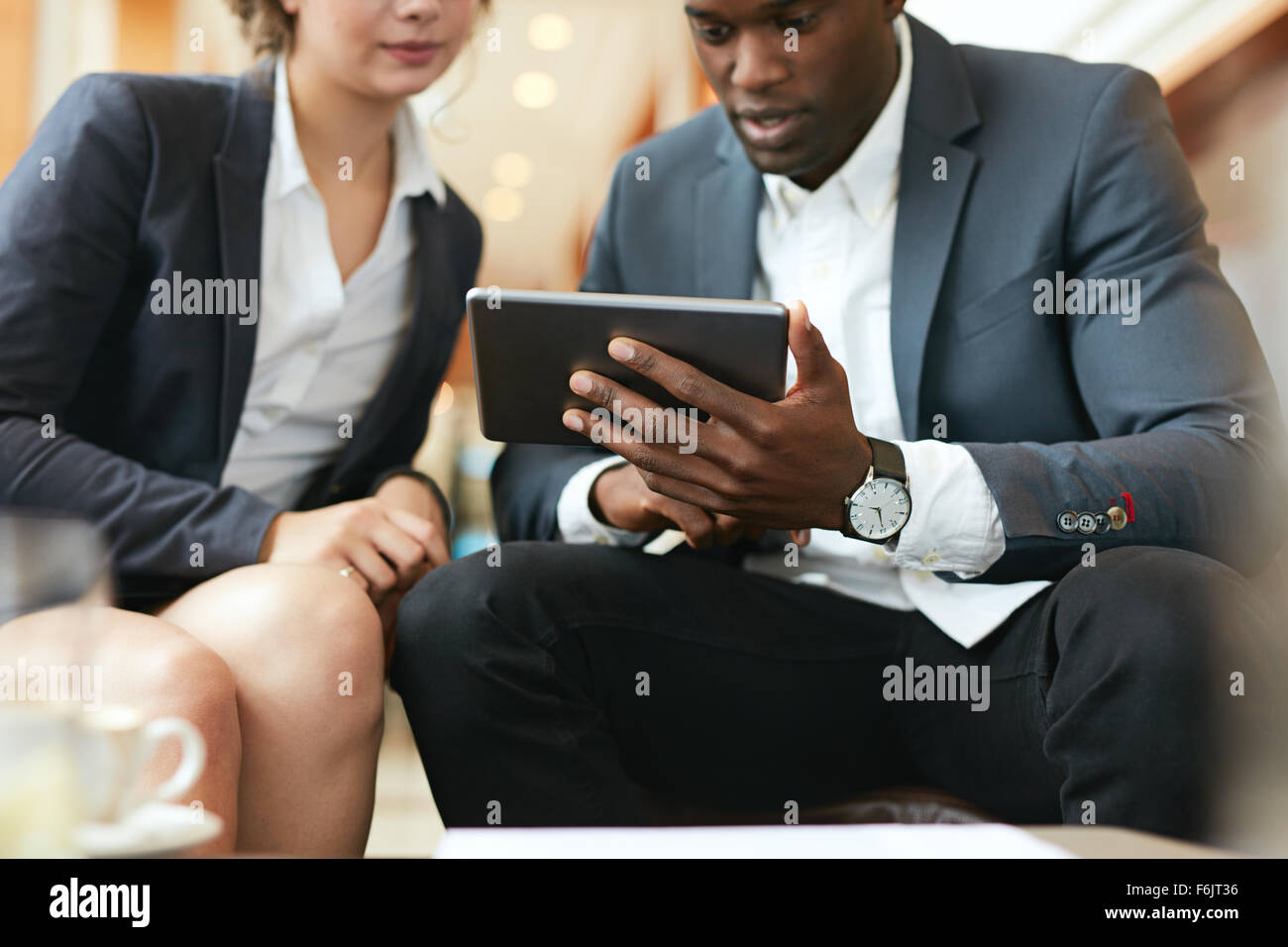 Close up shot of african business man showing something on digital tablet to his female colleague. Business people - Stock Image