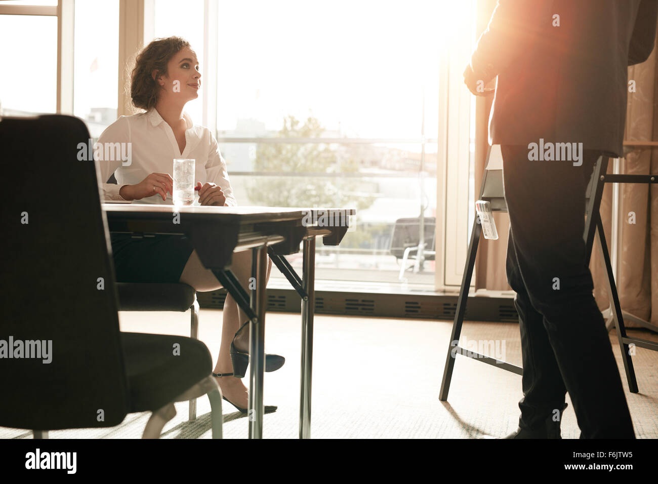 Shot of young female executive sitting at conference table with businessman showing presentation. Businesspeople - Stock Image