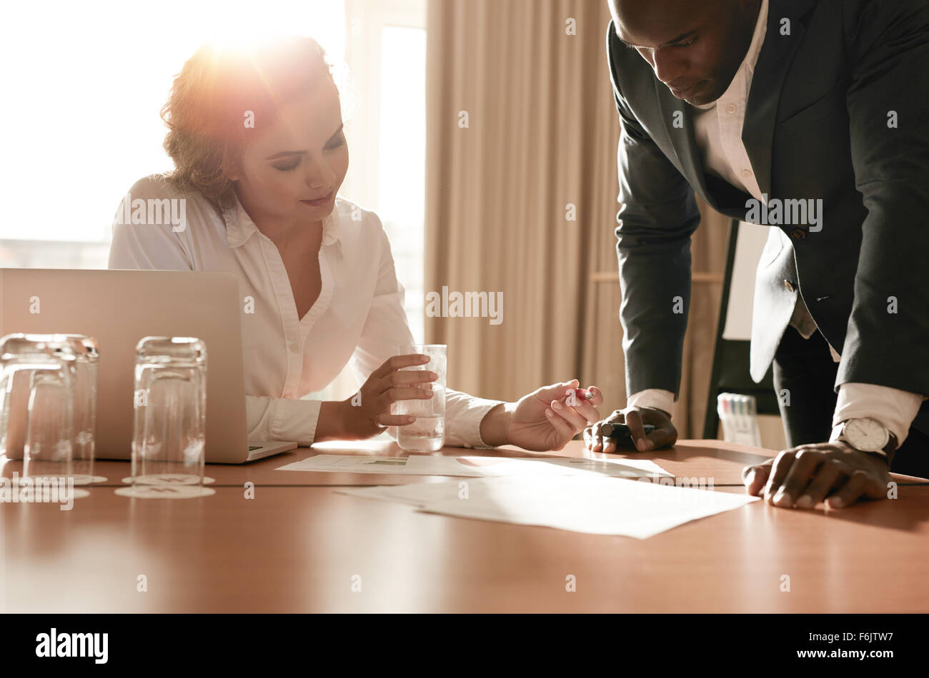 Two young business colleagues working on some business ideas. Entrepreneurs analyzing business reports on conference - Stock Image