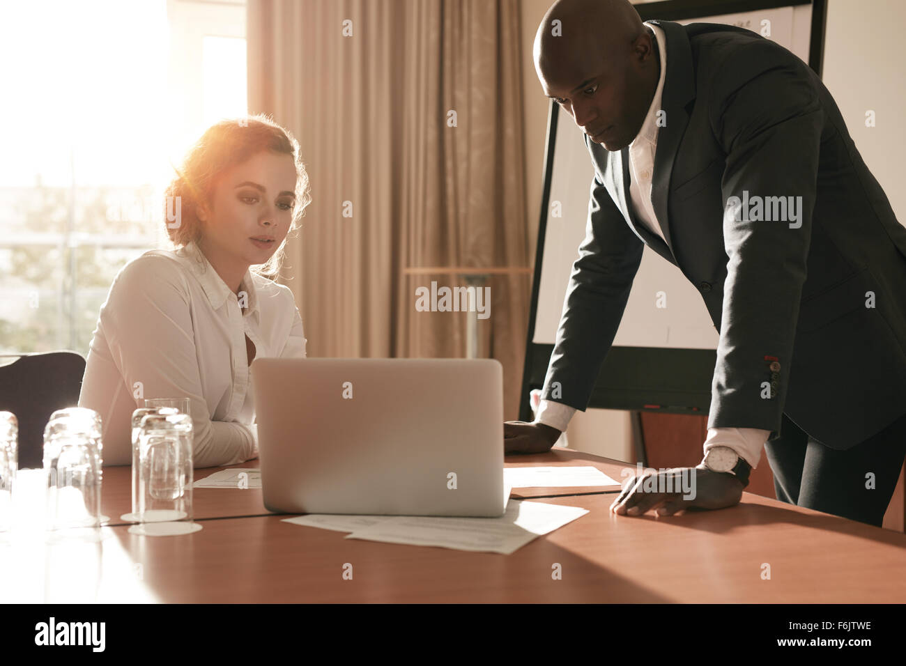 Two business people looking at business plan on laptop. Businessman and businesswoman in conference room working - Stock Image