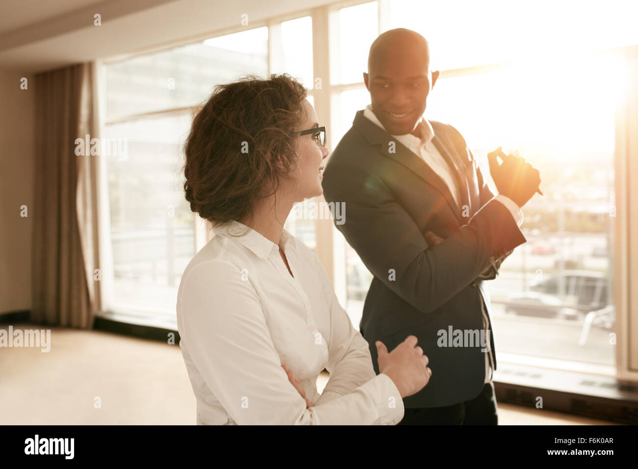 Two young business people discussing work during a business presentation in conference room at a hotel. Smiling - Stock Image