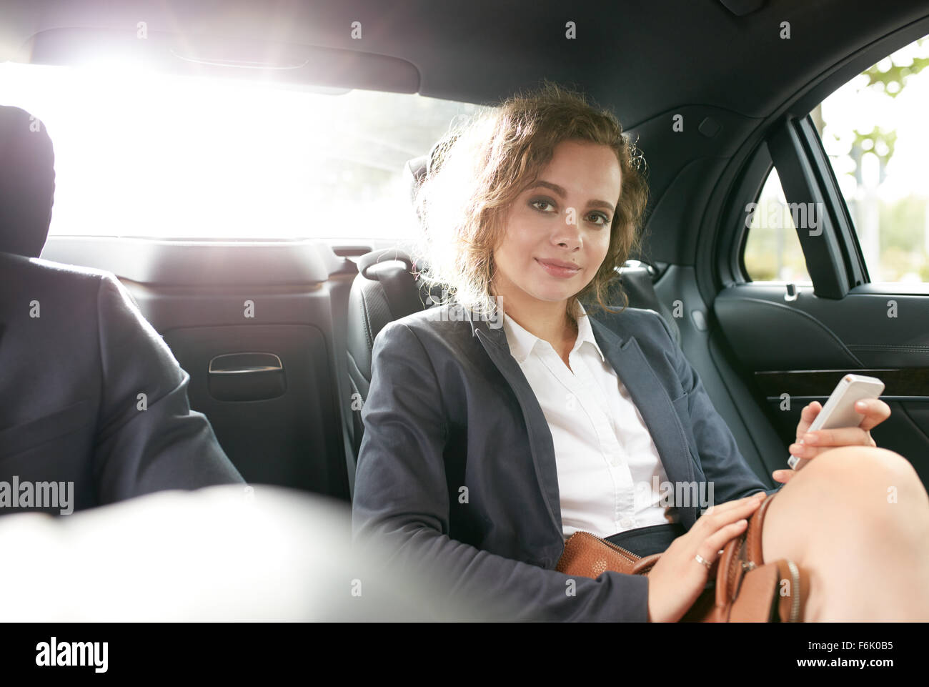 Portrait of confident businesswoman in back seat of car with her cell phone in hand looking at camera. - Stock Image