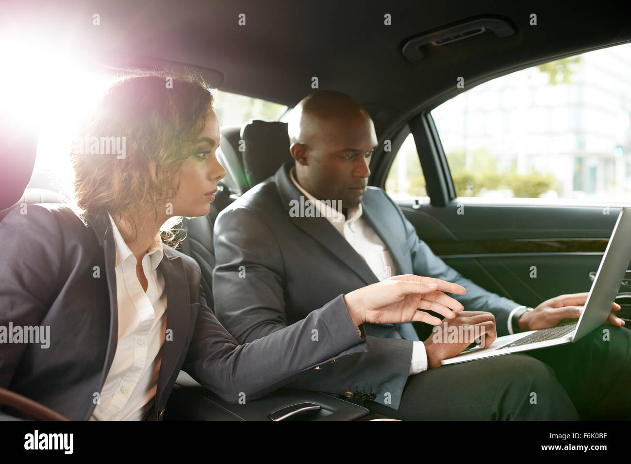 Shot of young business associates travelling to work in the luxury car on the back seat working on laptop. Discuss - Stock Image
