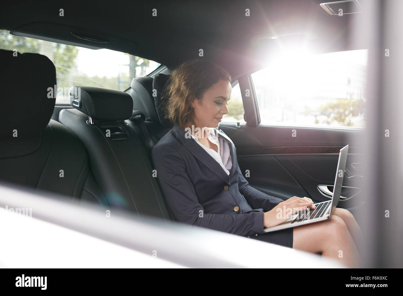 Shot of young businesswoman working on laptop inside a car. Business associate travelling to work in a car checking - Stock Image