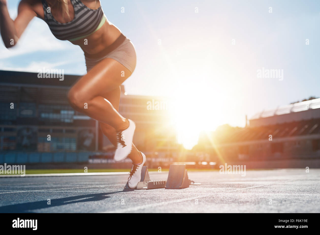 Cropped shot of young female athlete launching off the start line in a race. Female runner started the sprint from Stock Photo