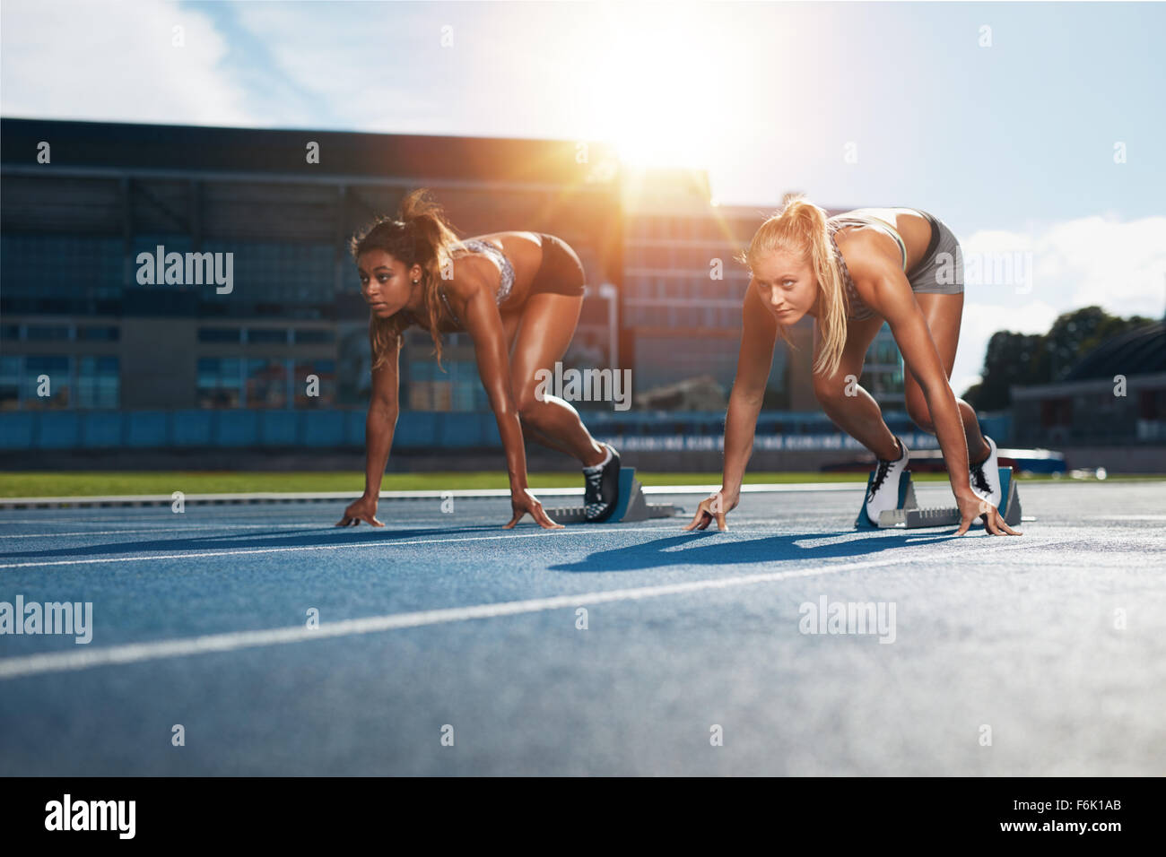 Two female athletes at starting position ready to start a race. Sprinters ready for race on racetrack with sun flare. - Stock Image