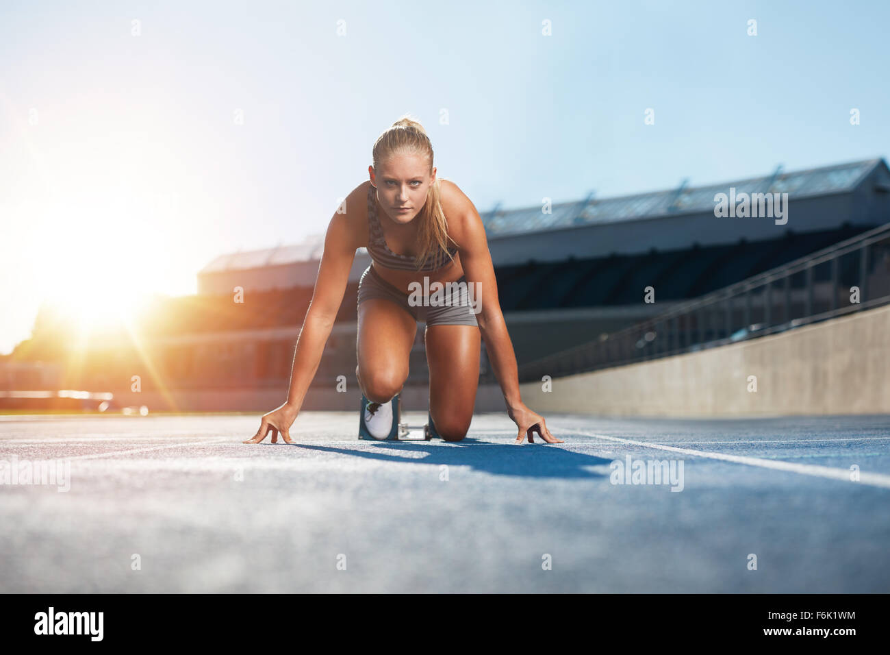 Confident young female athlete in starting position ready to start a sprint. Woman sprinter ready for a run on racetrack - Stock Image