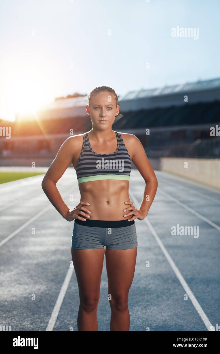 Fit young woman after run on stadium race track. Confident female athlete standing with her hands on hips looking - Stock Image