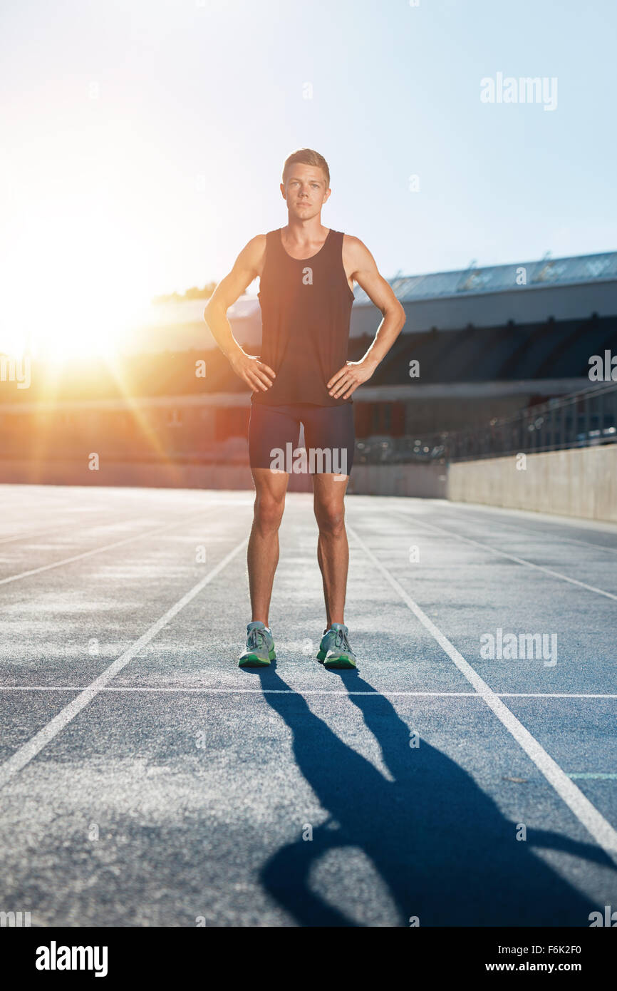 Full length shot of professional male athlete standing with his hands on hips looking confidently at camera. Sprinter Stock Photo