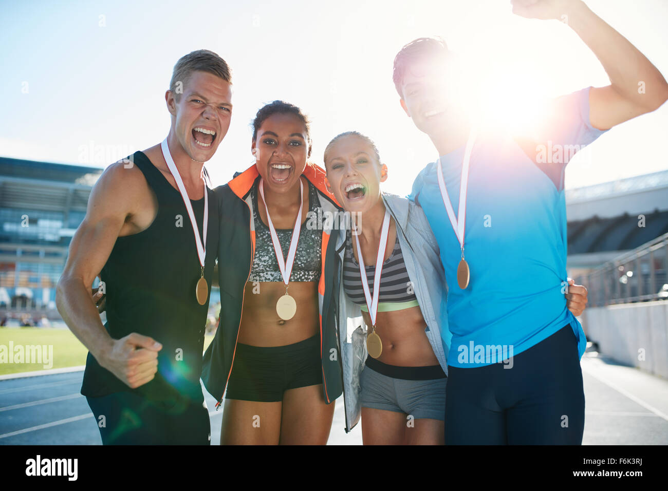 Portrait of ecstatic young runners with medals celebrating success in athletics stadium. Young men and women looking - Stock Image