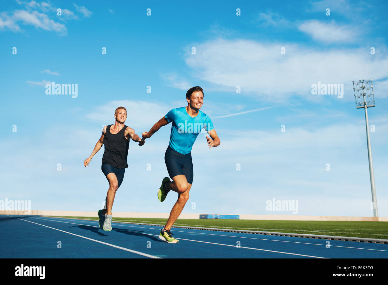 Shot of professional male athletes passing over the baton while running on the track. Athletes practicing relay - Stock Image