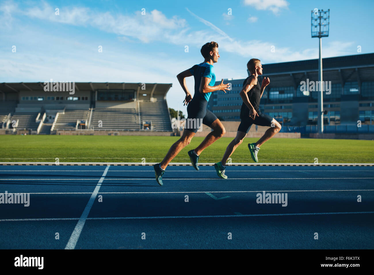 Two young men running on race track. Male professional athletes running on athletics race track. - Stock Image