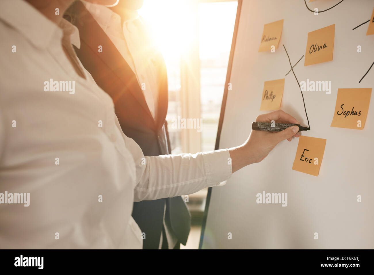 Cropped shot of business people making pairs of employees for making efficient sales team. Woman pairing sticky - Stock Image