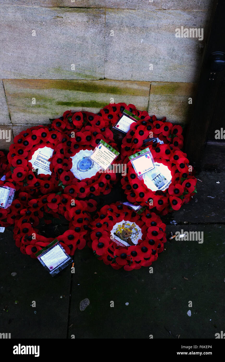 A pile of poppy wreaths in a pile on the ground in Brighton. - Stock Image