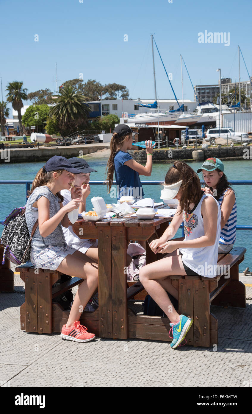 Schoolchildren enjoy a fish and chip lunch during an educational visit to Simon's Town home of the South African - Stock Image