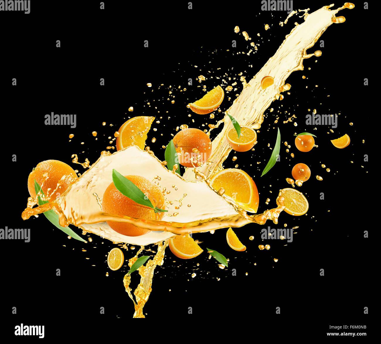oranges with juice splash on the black background - Stock Image