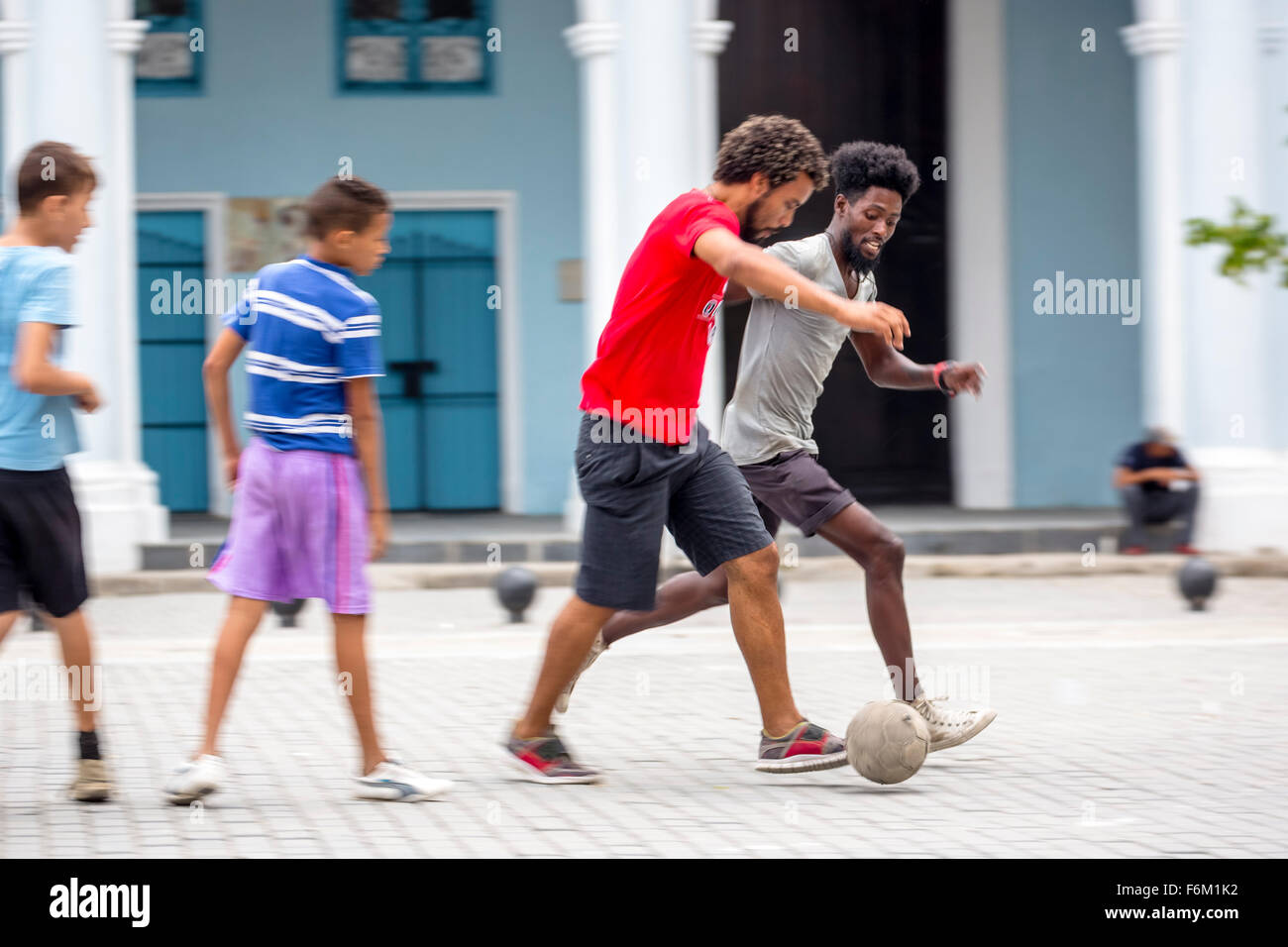 Cuban youths playing football in the town square, movement, in a marketplace, Street Scene, La Habana, Cuba, Caribbean - Stock Image