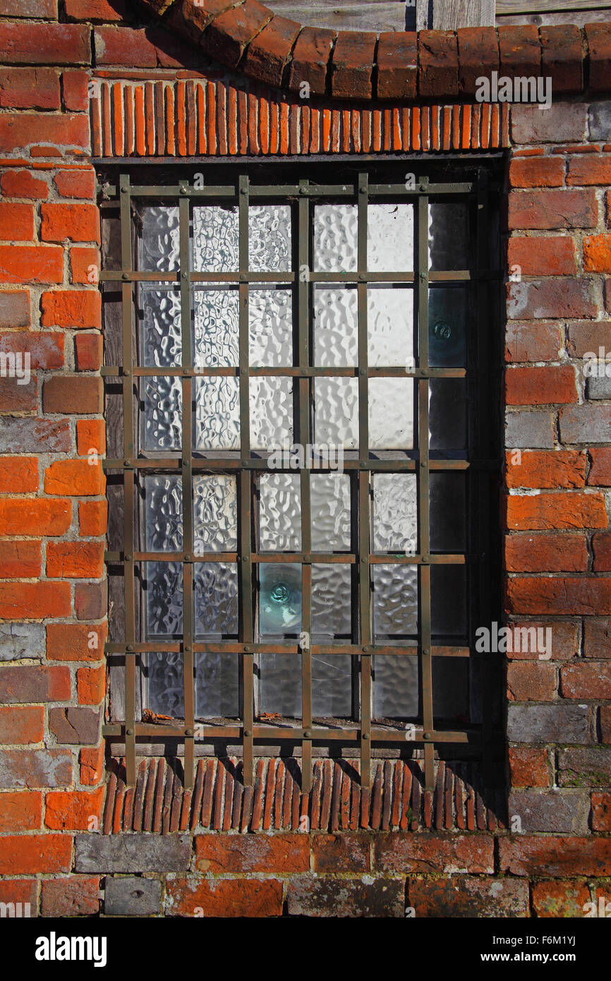 A very old barred leaded glass window with hand blown glass and old brickwork surrounding it. - Stock Image