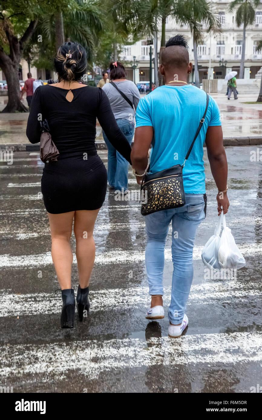 extravagant Cuban couples on the crosswalk, street scene, rain, shopping bags, black dress, Cuba, North America, - Stock Image