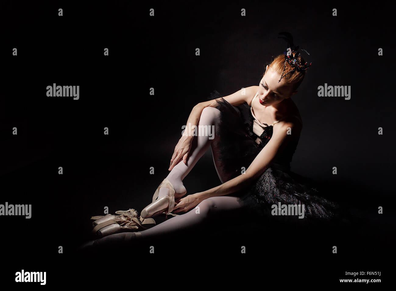 Slim ballerina in a black corset and black tutu tying pointe shoes. Classical Ballet. Photography in low key. - Stock Image