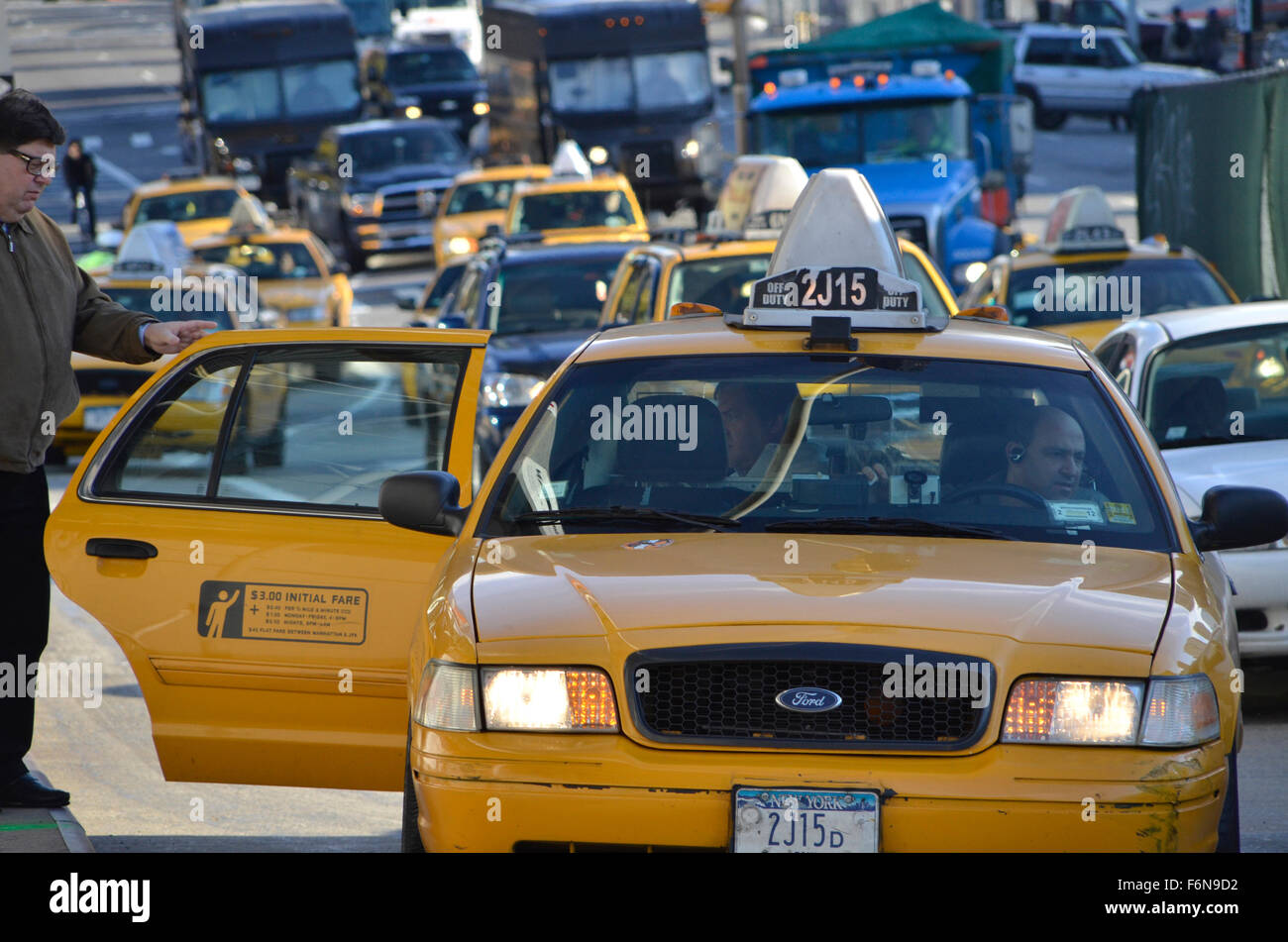 Taxicab letting off passengers in busy New York City - Stock Image
