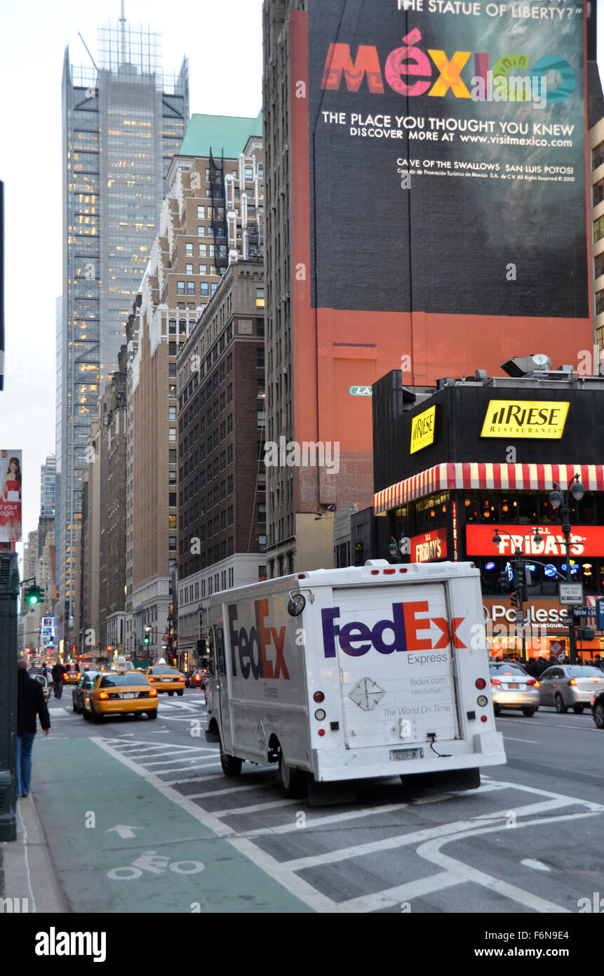a fedex truck drives past a large sign advertising mexico on a street in new york - Fedex Garden City