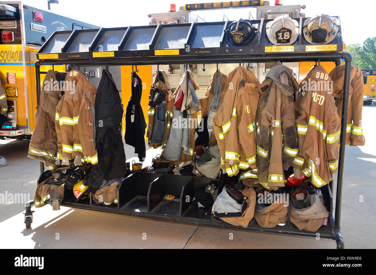 firefighters turnout gear hanging on racks - Stock Image