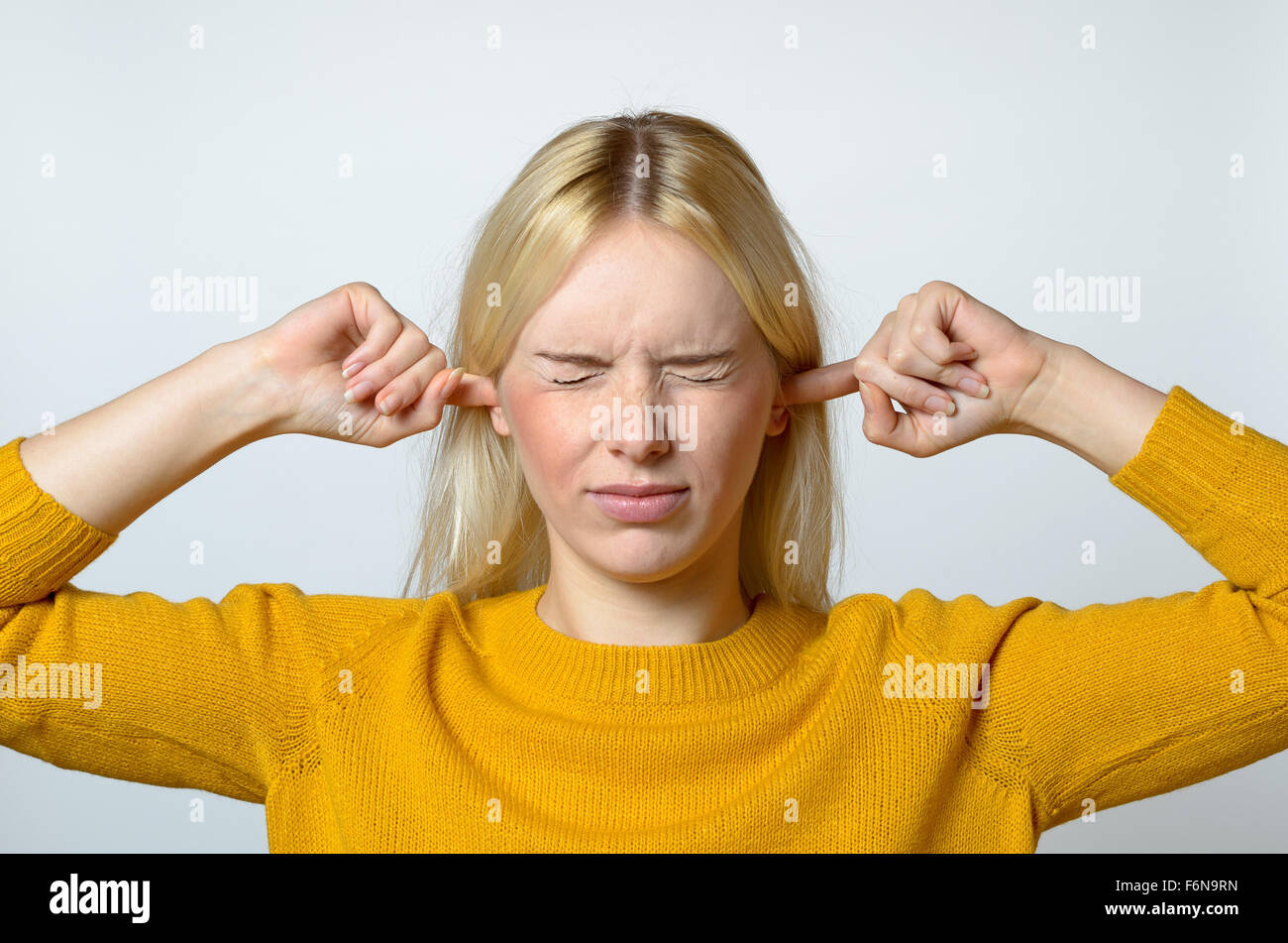 Close up Disgusted Young Woman Covering her Ears with Fingers, with Eyes Closed, Against Gray Background. - Stock Image