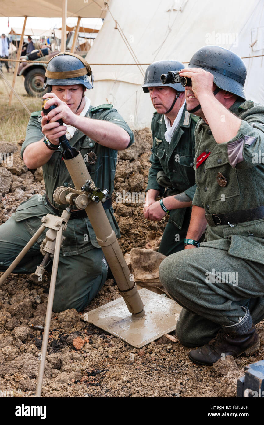 World war two re-enactment. Three Wehrmacht soldiers in dug-out, about to fire 8cm light trench mortar with officer - Stock Image