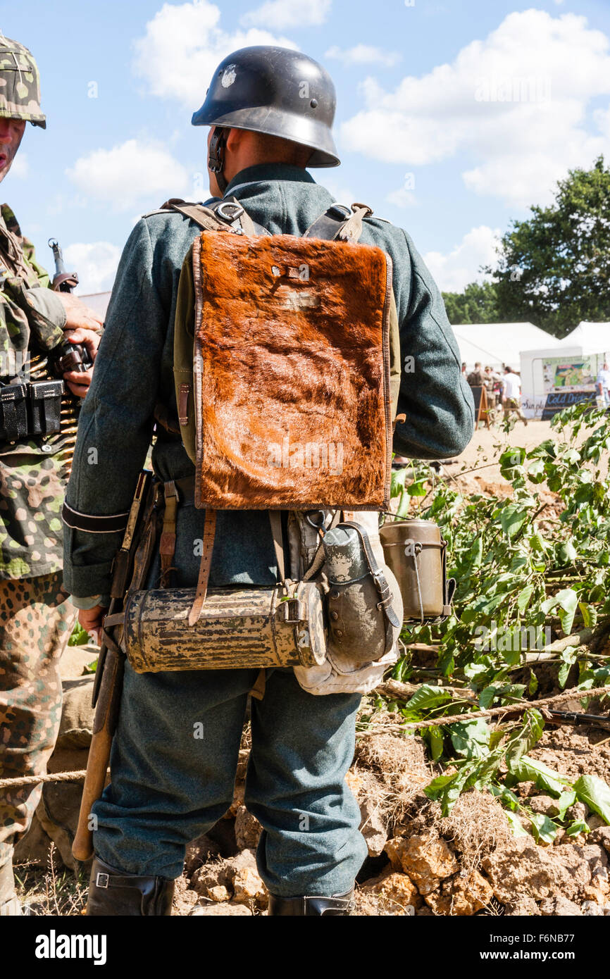 World war two re-enactment. Wehrmacht German soldier, rear view, showing uniform, kit and Poni fur backpack, gas - Stock Image