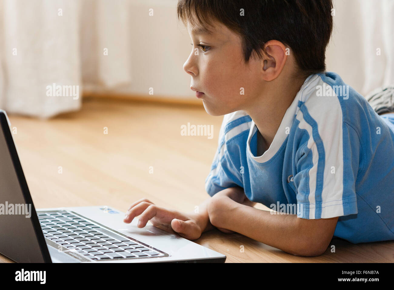 Side view of Caucasian child, boy, 7-8 year old, laying on floor using laptop computer. Fingers on scroll pad and - Stock Image