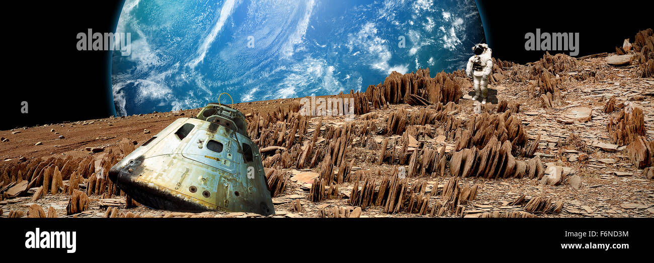 An astronaut surveys his situation after being marooned on a barren and rocky moon. An alien, and water covered - Stock Image